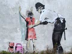 banksy-girl-being-frisked-by-policeman
